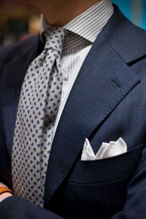 Wool paisley print tie paired with striped shirt, navy suit, and white  linen pocket square