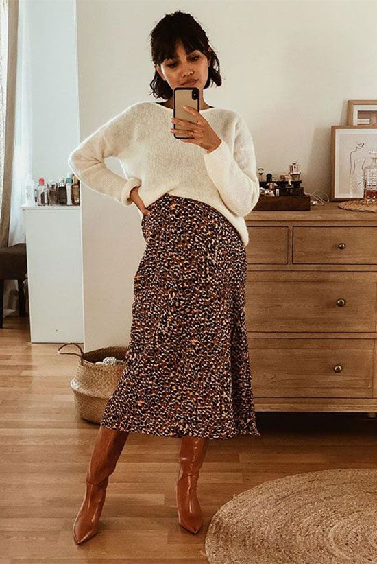 6 Reasons To Love The Midi Skirt And Boots Combo: Fashion Blogger 'Sherlock Diary' wearing a white oversized sweater, a leopard skirt and brown tall boots. Fall outfit, spring outfit, street style, casual outfit, casual style, blogger style, fashion 2019, fashion trends 2019, midi skirt outfit, #fashion2019 #streetstyle #casualstyle #fallstyle #springstyle #ootd #trendingrn
