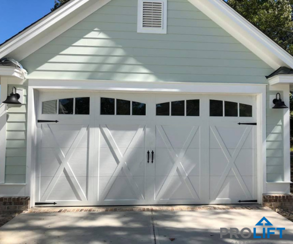 This White Carriage House Garage Door Has The Look Of Painted Wood And Has The Charm Of An Old F Garage Door Styles Carriage House Doors Carriage House Garage