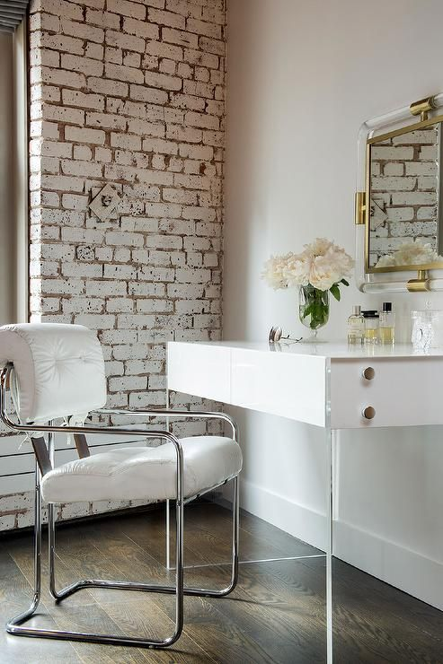 Dressing room featuring whitewashed exposed brick walls alongside a