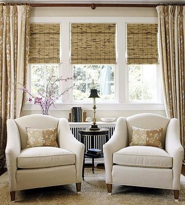 Patterned curtains, cream chairs with wood legs, and wooden blinds