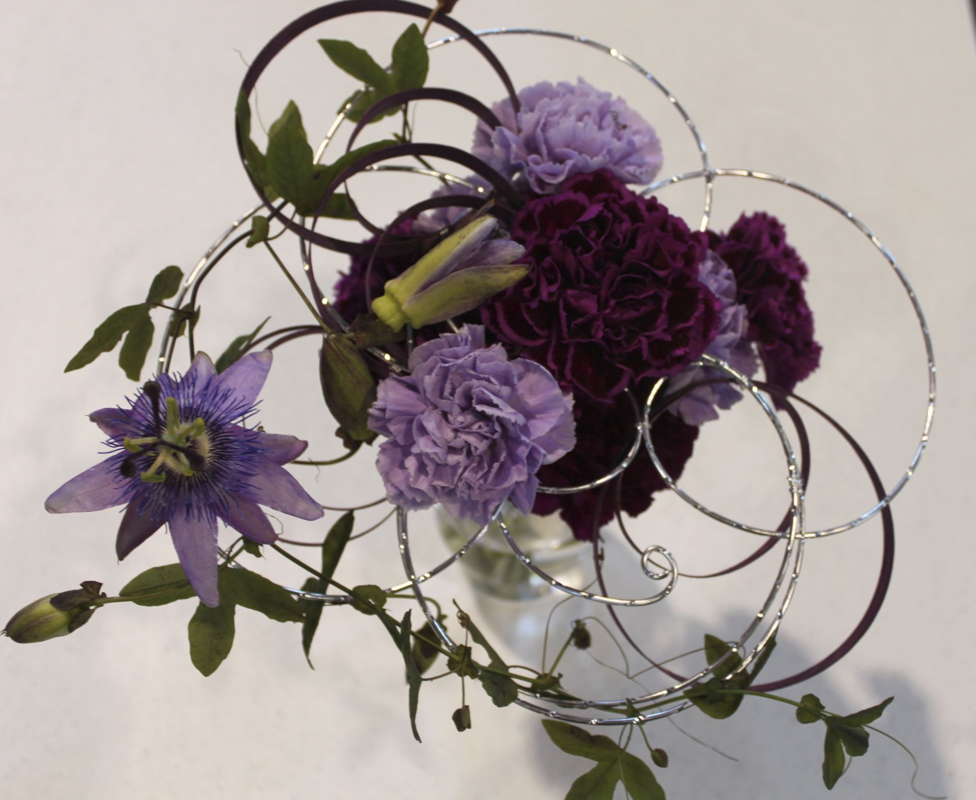 Dianthus and passion flower bouquet on diamond wire armature with aubergine flat cane circles