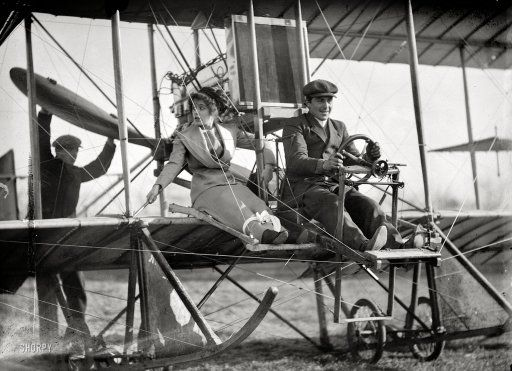 """Washington, D.C., or vicinity circa 1911. """"Senorita Lenore Riviero with Antony Jannus in Rex Smith aeroplane."""" Please fasten your seatbelts (or skirts) while we prepare for departure. Tony Jannus, the pioneering but short-lived Washington aviator, a few years before his final flight landed him somewhere at the bottom of the Black Sea."""