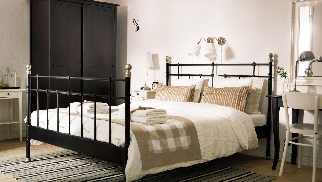 Una habitación de hotel con una cama negra y ropa de cama en beige ...