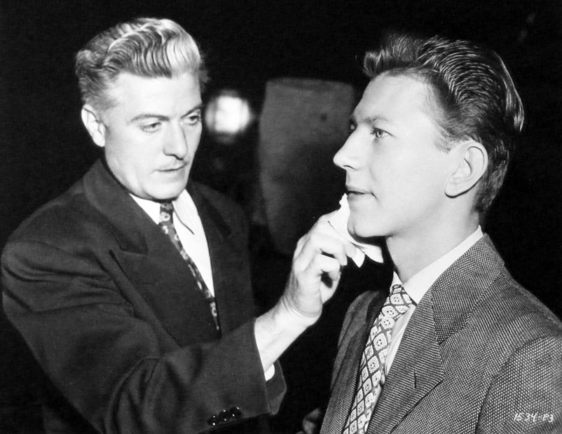 """Donald O'Connor getting a touch-up on his make-up done for """"Something in the Wind"""". Make-up artist, Don Donaldson."""