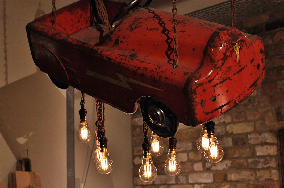 Bright Goods LED filament GLS Joseph light bulbs hanging from a industrial, vintage car at Maggie & Rose, Kensington.
