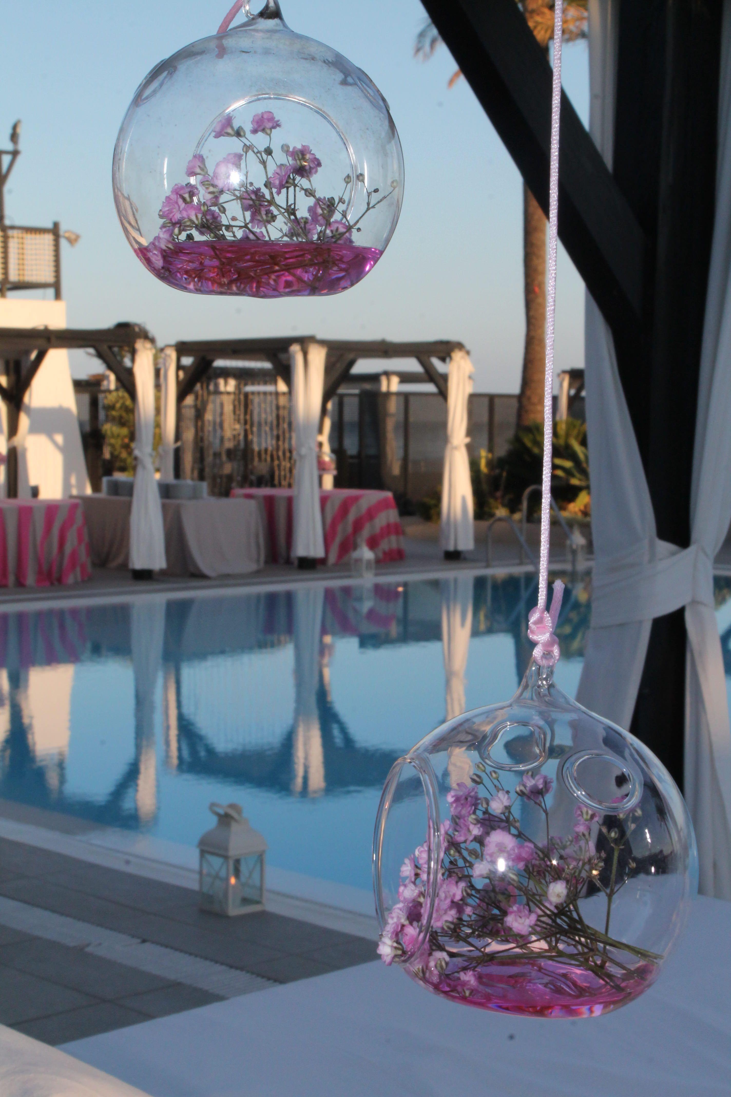 originales recipientes de cristal con adornos florales para decorar tu boda junto a la piscina del