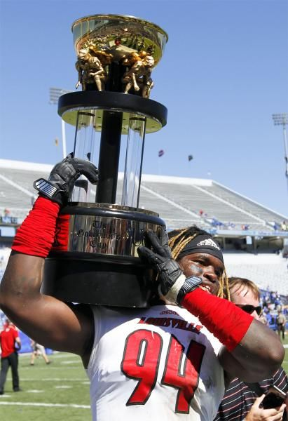 Louisville S Lorenzo Mauldin Carries The Governor S Cup Trophy Off The Field After Louisville Defeated Kentucky 2 Louisville Cardinals Louisville Ncaa Football