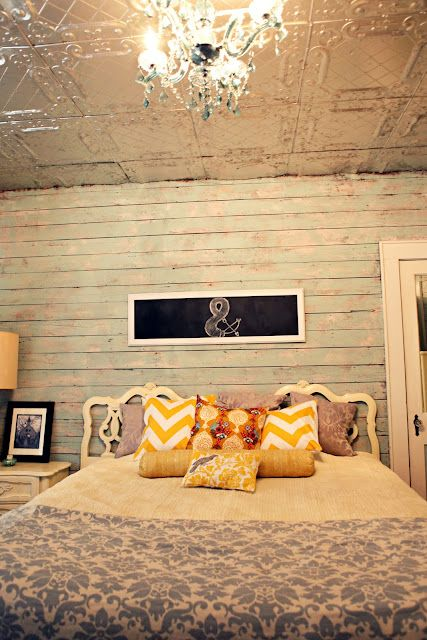 White washed wood plank walls, tin ceiling, pillows, chandelier ...