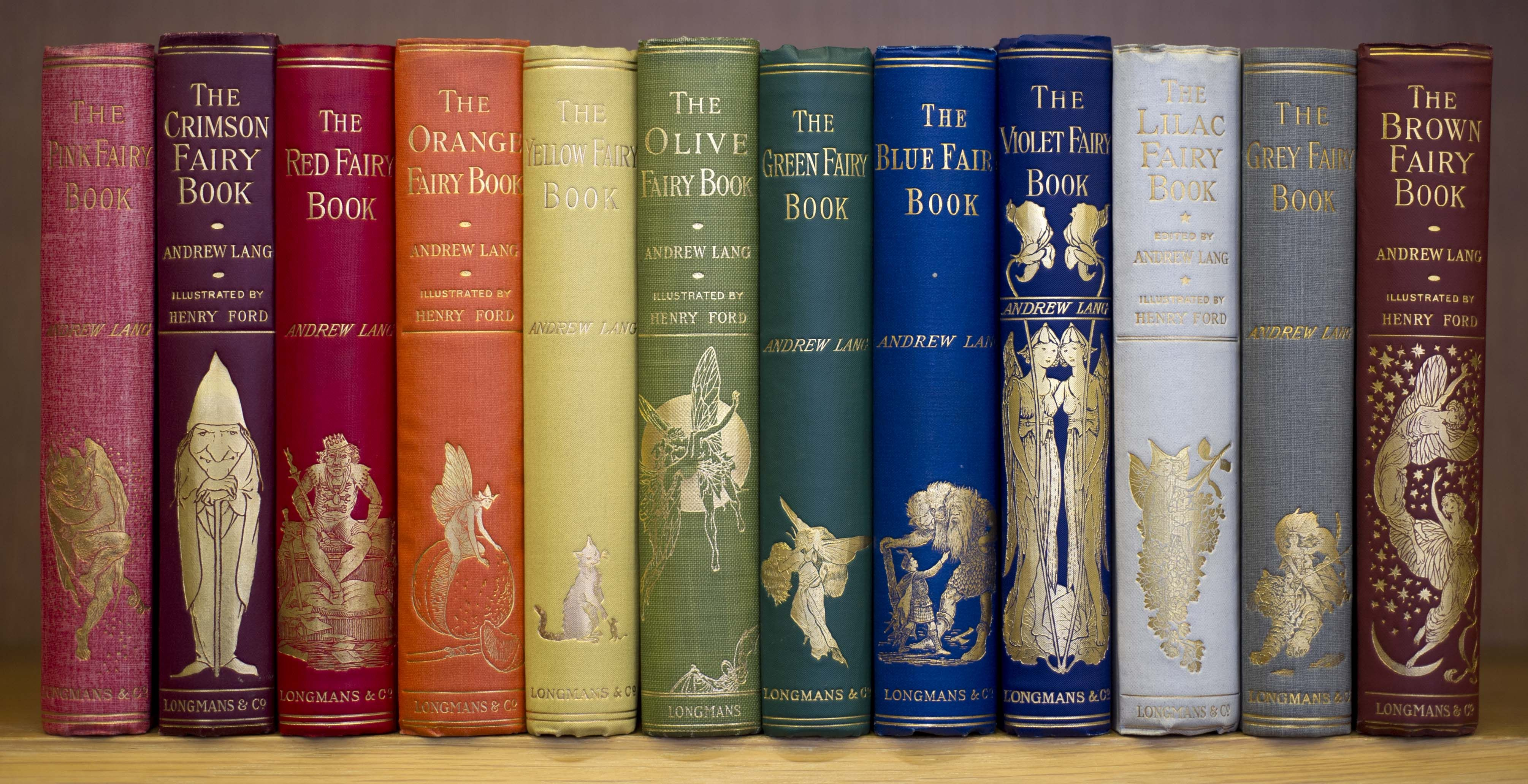 """A series of book spines, arranged in order of color to correspond with the colors of the rainbow. On each spine is a book title, beginning with """"The Pink Fairy Book"""" and """"The Crimson Faiasdk"""