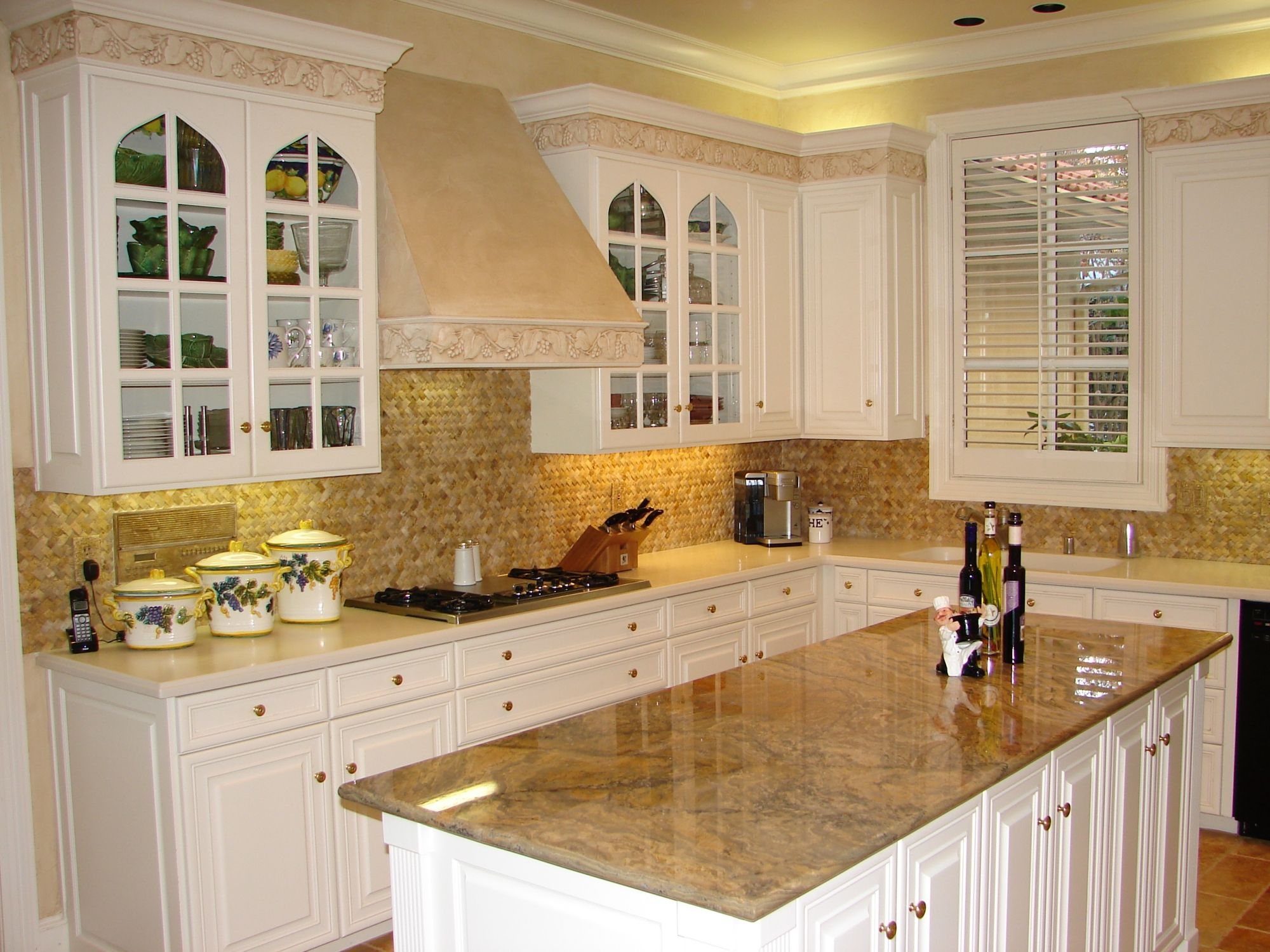 White Cabinets With Earth Tone Back Splash And Tan Granite