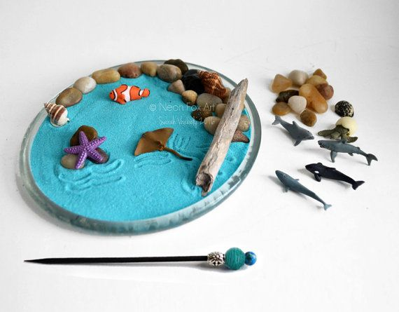 Made to Order: The pebbles, mini shells, and driftwood will vary slightly. Please see fourth photo for examples.  Miniature desktop zen garden featuring mini ocean figurines! With this DIY Zen Kit you can create your own little ocean scene. Leave just the sand or arrange the pebbles in the sand to create a little beach for the driftwood and sea shells. Create designs in the sand with the stylus and arrange the miniatures any way you like! Included with the ocean life miniatures are a small…