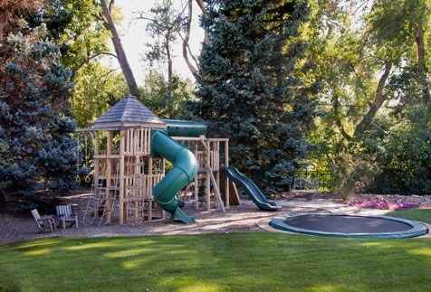Playground Surrounded By Trees With Sand Or Gravel With Sand Pit And A Levelled Trampolin Play Area Backyard Backyard Play Backyard Playset