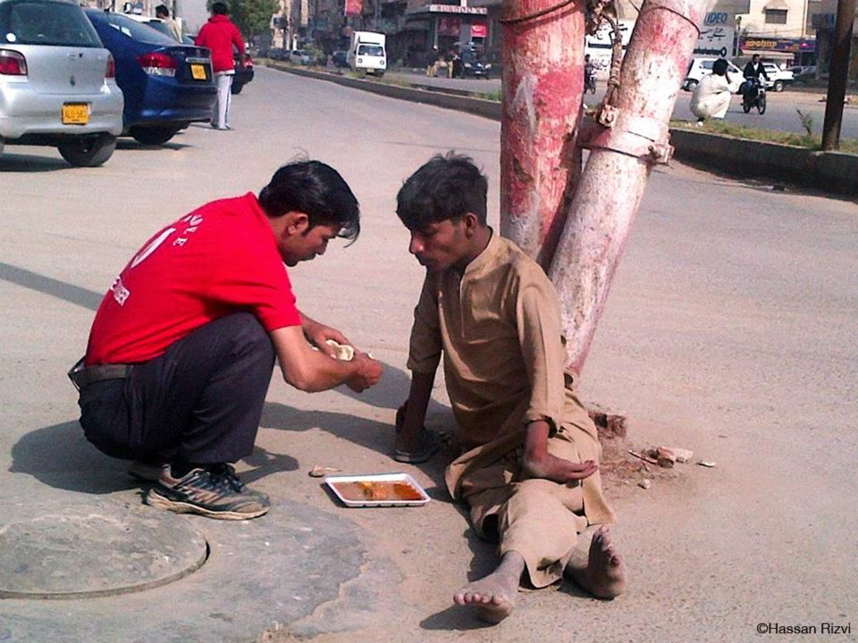 Waiter at a restaurant buys food and feeds disabled beggar with his own hands, in Karachi, Pakistan.