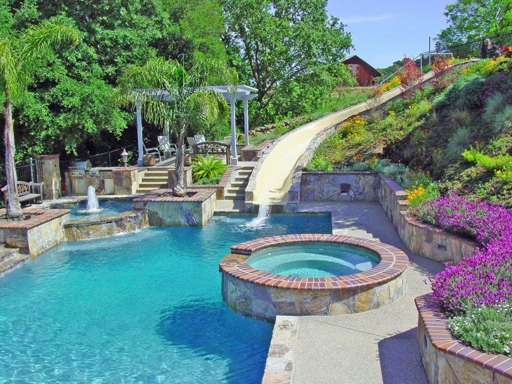 Swimming pool slides swimming pool and spa waterslide for Pictures of swimming pools in backyards