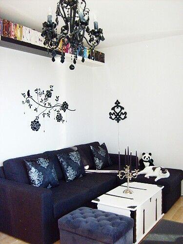 Black sofa,chandelier,and wallpaper