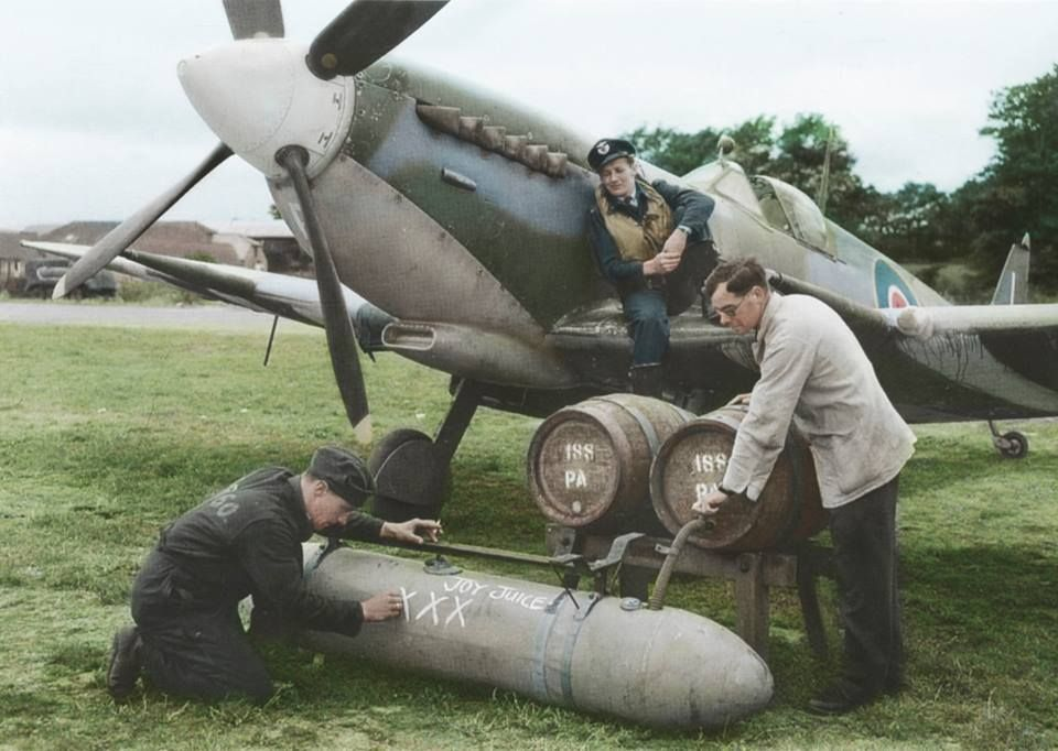 Tangmere, Sussex, July 1944: in front of a Spitfire IX of 332 (Norwegian) Squadron, a standard 45 gallon Typhoon/Hurricane 'Torpedo' jettison tank modified for use on the Spitfire (because of an expected shortage of 45-gallon shaped or slipper tanks) is filled with PA ale from two wooden casks supplied by the Chichester brewer Henty & Constable, for flying over to Normandy (Colourised by Tom Thounaojam)