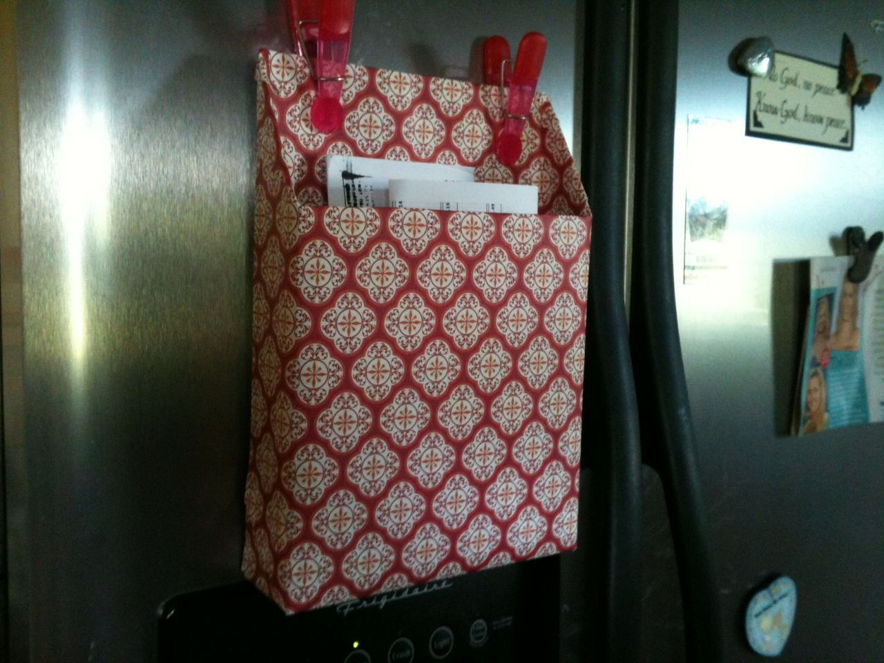 Cereal box covered in scrapbook paper with magnets on the side of the fridge.  I do love to organize!
