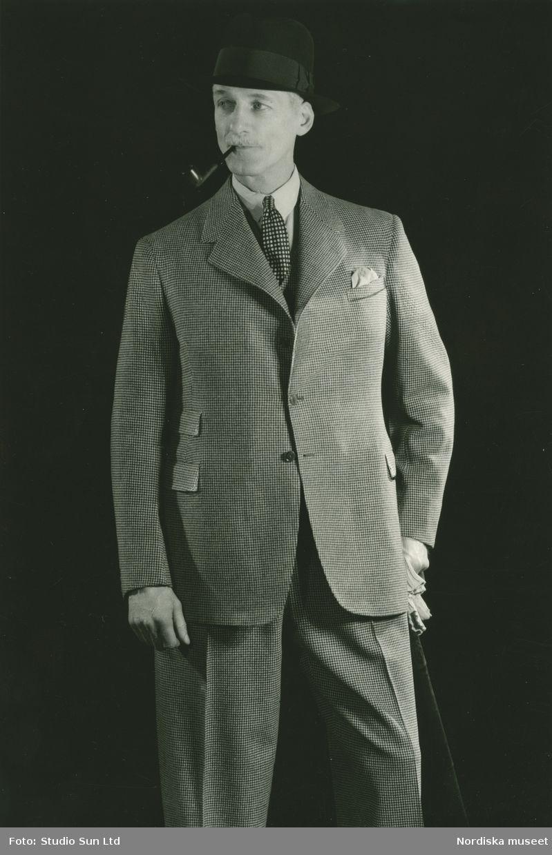 f169f8cd072c Porträtt av en man i kostym med hatt, pipa och käpp. Fotograf: Studio