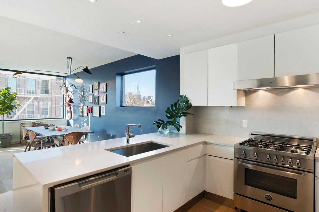 Simple white cabinets pair with stainless steel appliances for a ...