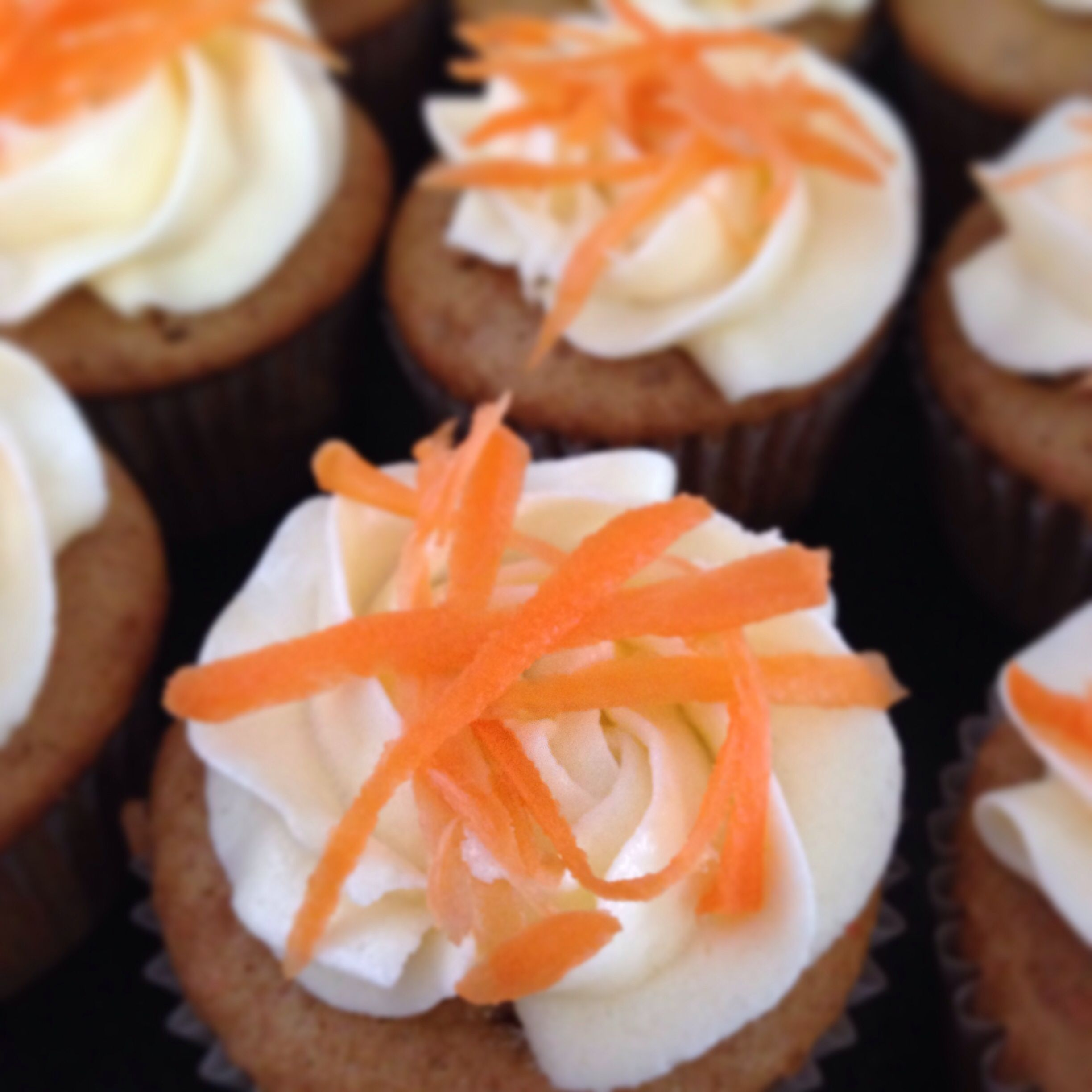 A carrot cake cupcake, frosted with a cheesecake inspired frosting. Topped with shredded carrot.