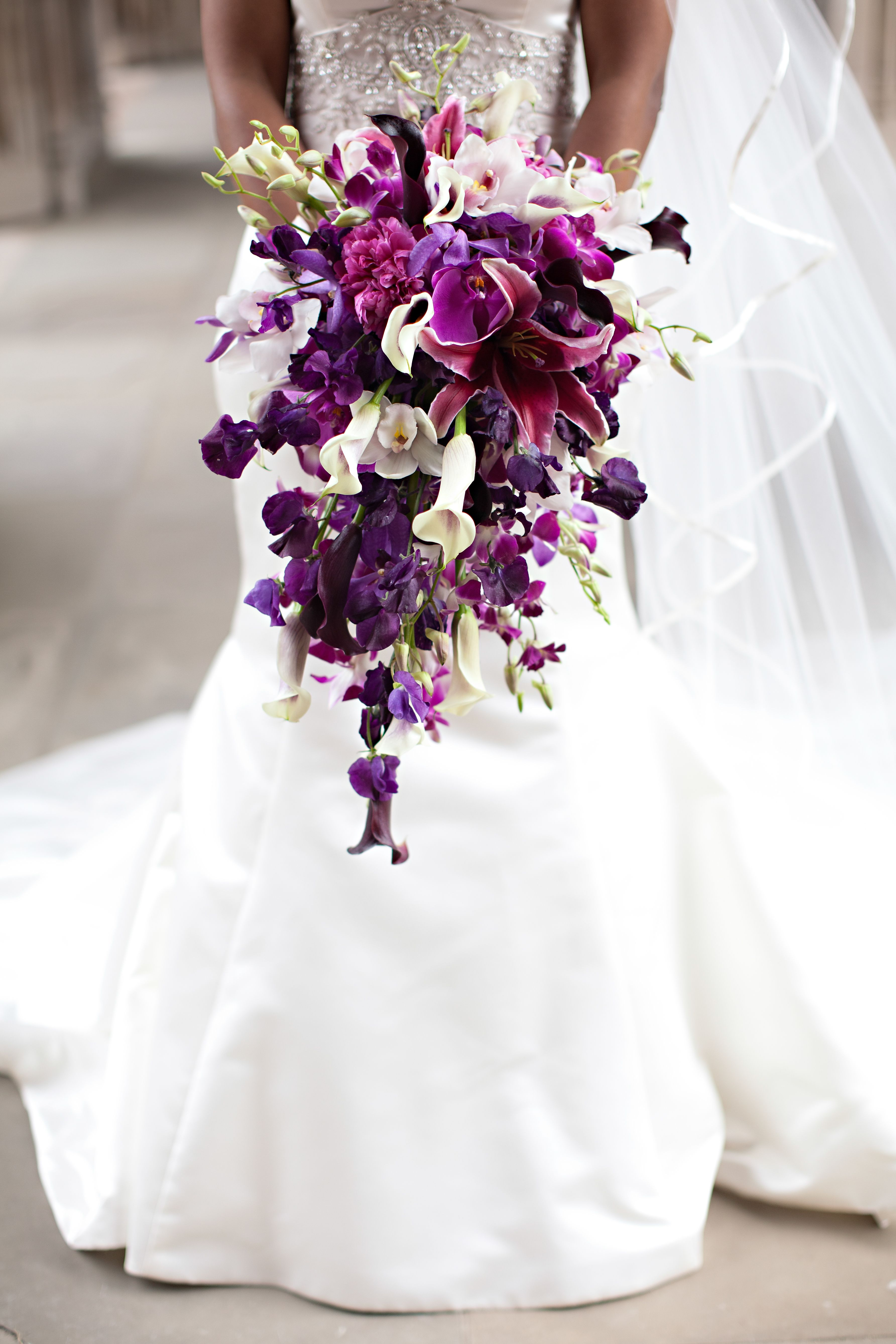 A beautiful purple inspired spray wedding bouquet filled with