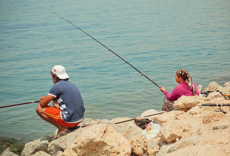 Woman with rod and man fishing on a bay with blue water of Aegean sea. KUSADASI, , #AFFILIATE, #fishing, #bay, #blue, #Woman, #rod #ad #aegeansea