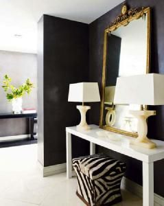 Entryway with Black wall white glossy parsons table and zebra
