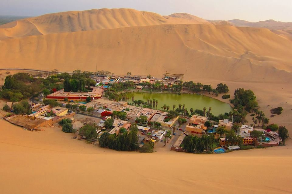 Huacachina, Perú.  En el desierto del suroeste de Perú se encuentra el pueblo de Huacachina, un pequeño oásis ubicado a 8km de la ciudad de Ica.Este lugar cuenta con la curiosidad de hallarse rodeado de dunas de arena por kilómetros y kilómetros