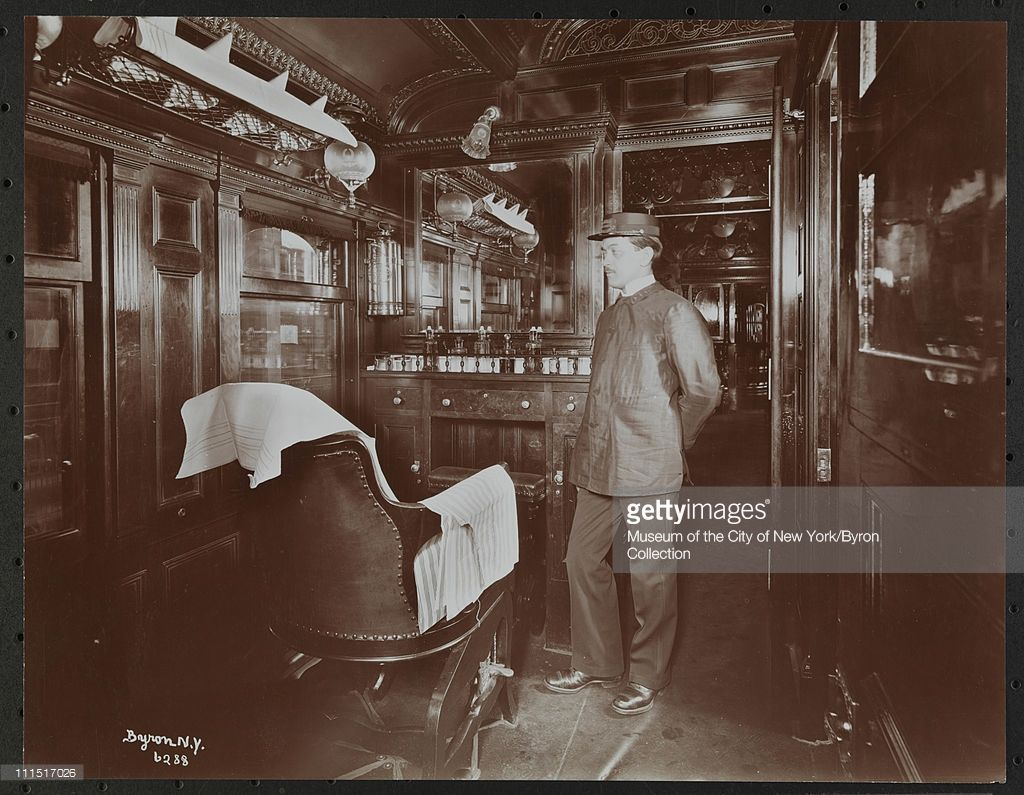 Barber in the barber shop on board a train of the Erie Railroad Co, New York, New York, 1899.