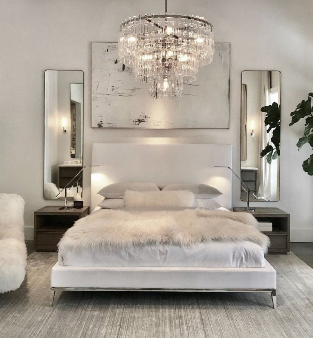 Luxury bedroom with white bed  white walls  chrome assents  crystal chandaleer  and sheepskin blanket  cozybedroom  glamdecor  dreambedroom  bedroomgoals #blackapartmentdecor #apartmentdecor