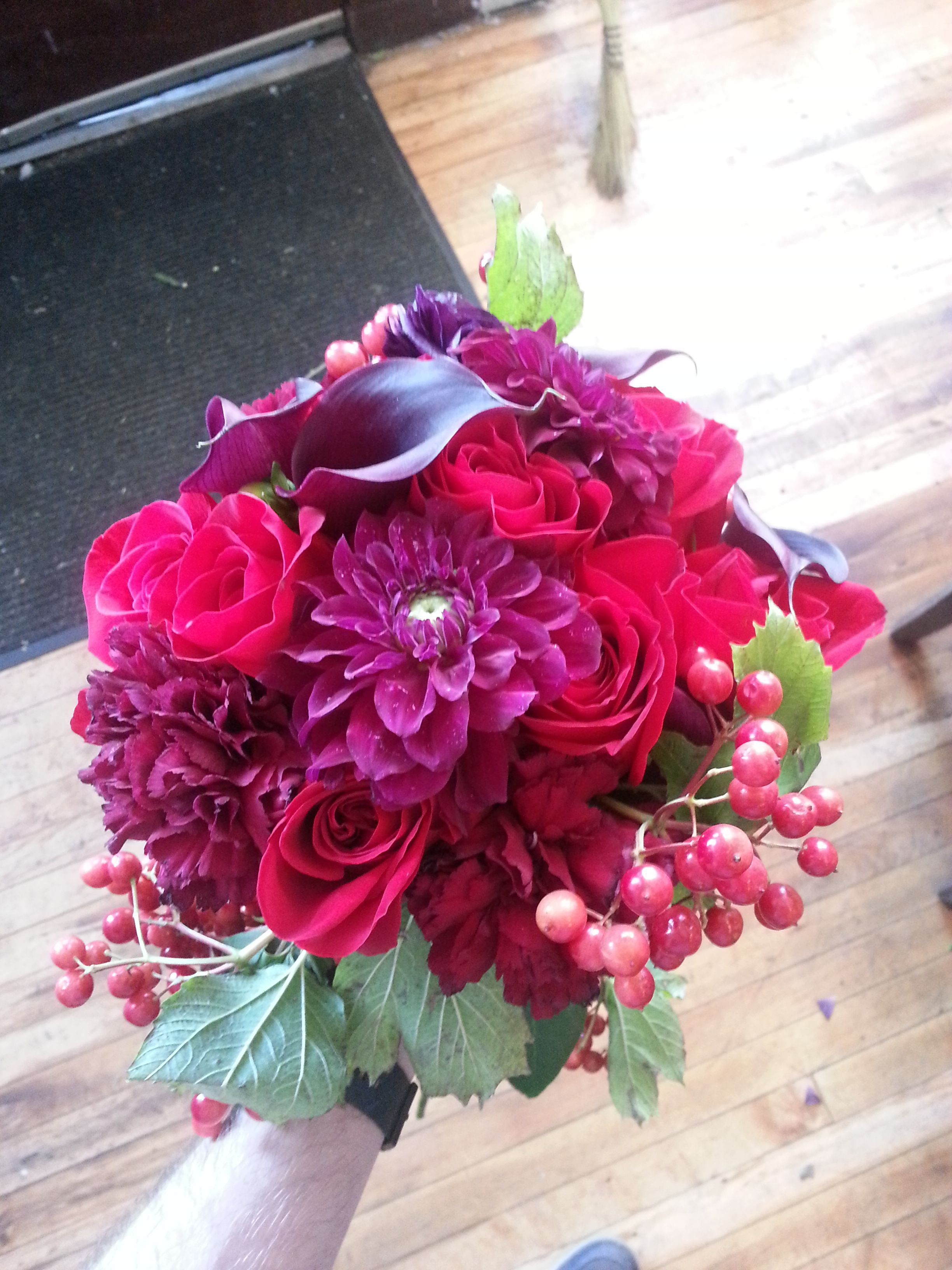 Red and burgundy wedding bouquet using roses, mixed berries, and ...