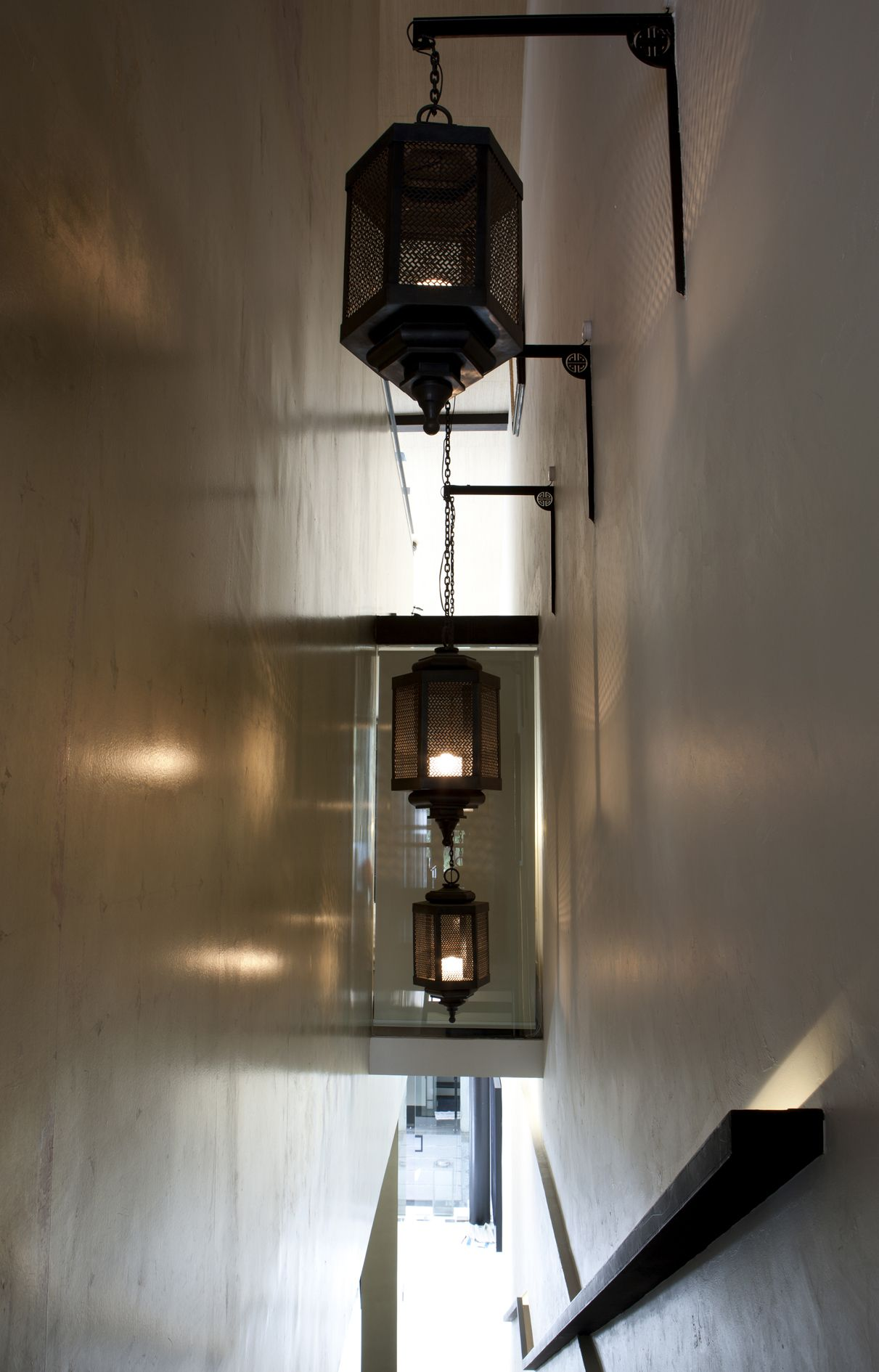 Residential bronze pendant lights with custom made wall brackets perspective in the staircase shophouse singapore