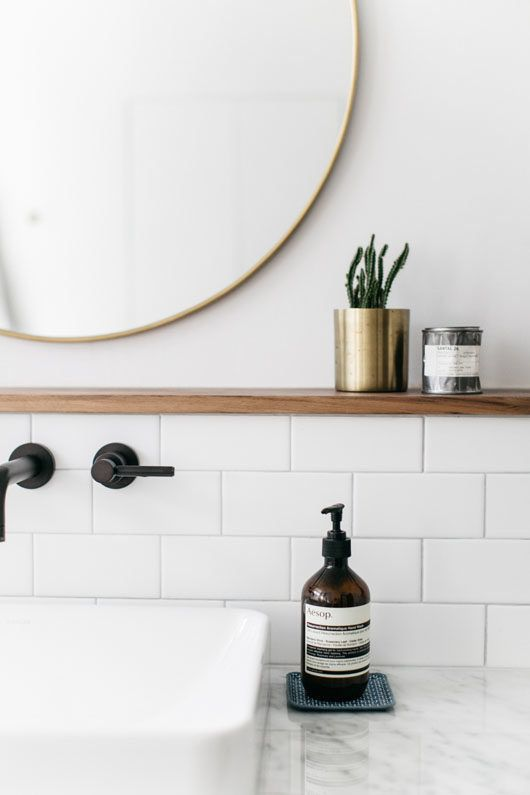 Modern Minimal Bathroom // White Subway Tile, Gold Framed Round Mirror,  Black Fixtures, Brown Wooden Shelf, Gold Planter