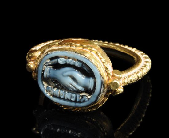 Late Hellenistic Blue Agate Cameo Of Two Clasped Hands Set Into An Antique Gold Ring With The Greek Inscription OMONOIA Together