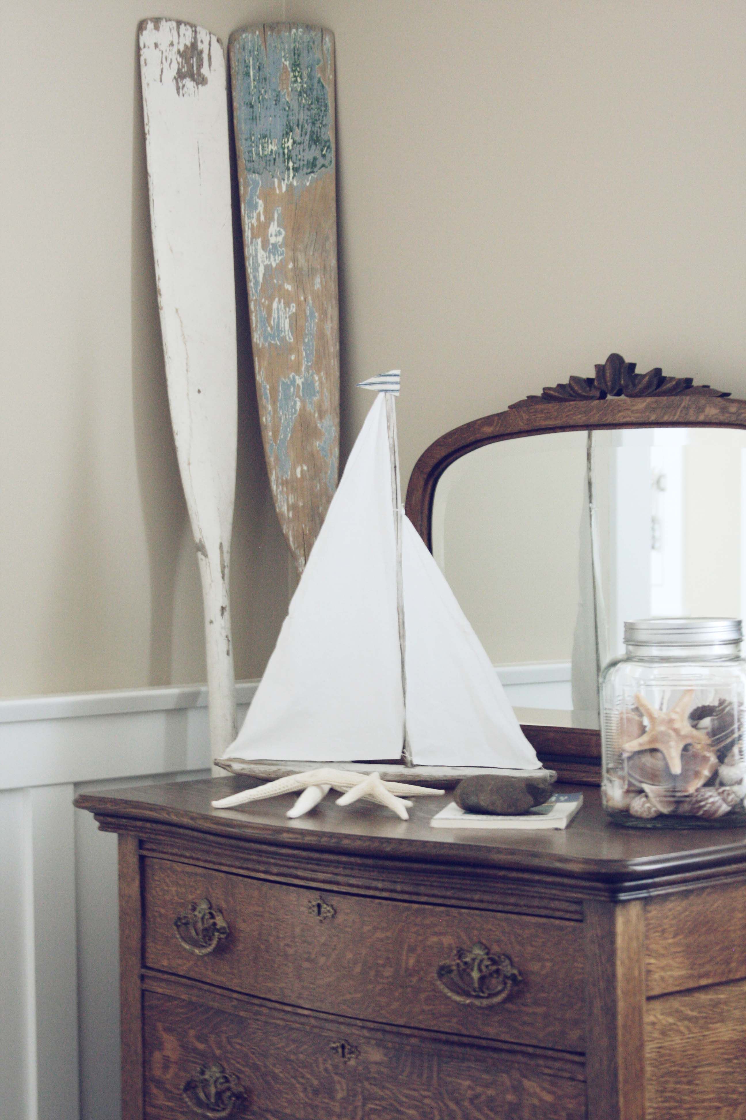 Weathered Oars In The Corner With A Toy Sailboat Seashells And