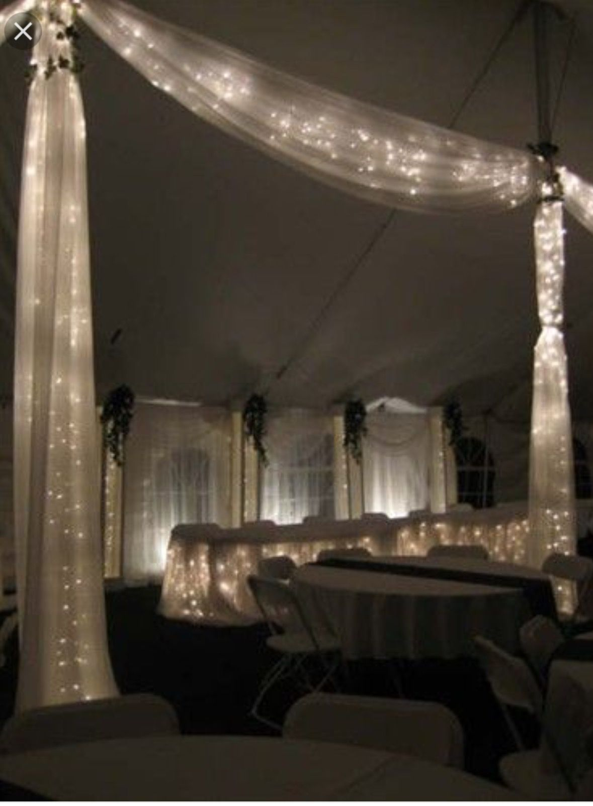 White Lights Wrapped In Tulle Decorating Tent Poles