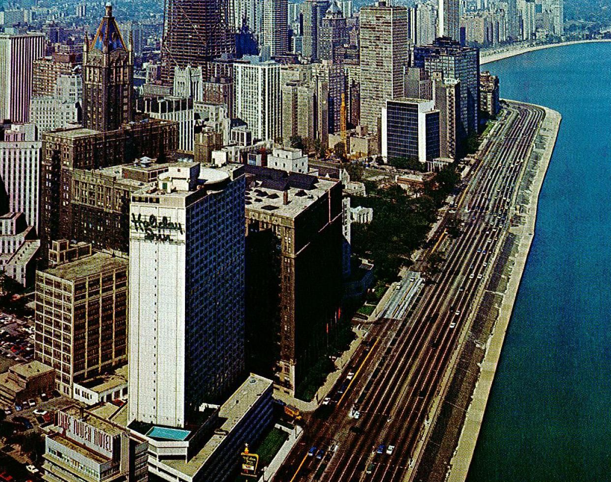 Late View Of The Holiday Inn Lake Shore Drive In Downtown Chicago. The  Blue Peaked Building In Back Of It Is The American Furniture Mart.