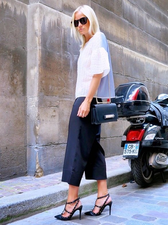 Celine Aagaard of Hippie Hippie Milkshake wearing a white top with bell sleeves, black culottes, and black heels