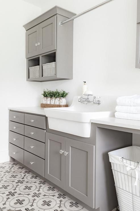 Gray shaker laundry room cabinets with glass knobs surrounding a white apron sink topped with white quartz countertops. #graylaundryrooms