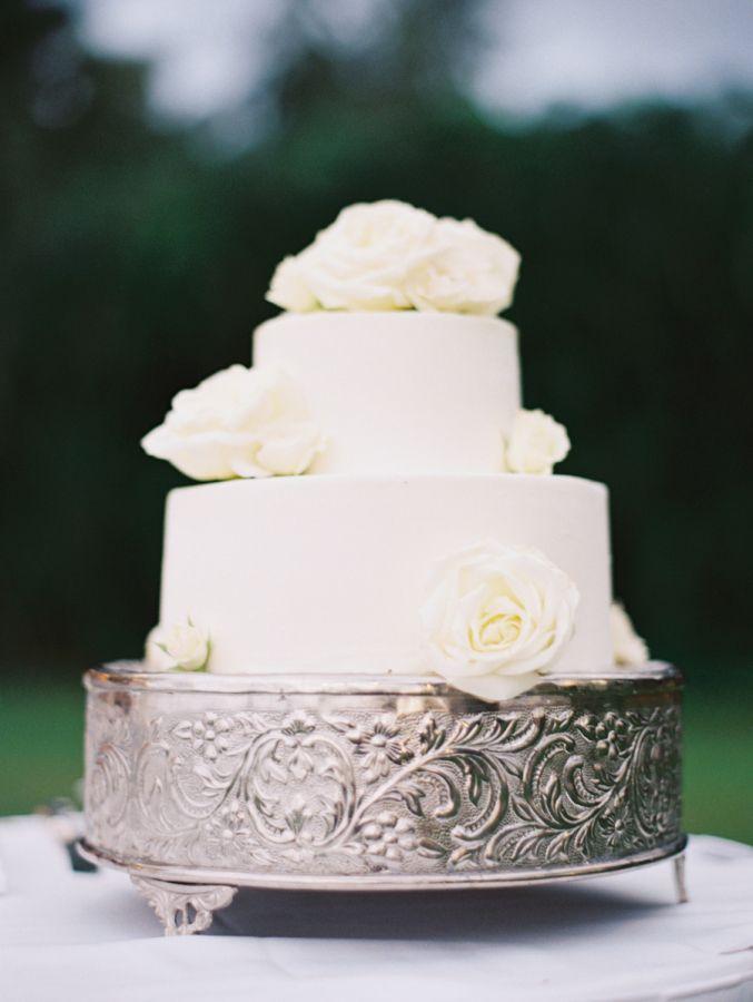 Classic white rose topped wedding cake: http://www.stylemepretty.com/destination-weddings/hawaii-weddings/2016/01/14/elegant-cliffside-wedding-in-hawaii/ | Photography: Wendy Laurel - http://www.wendylaurel.com/
