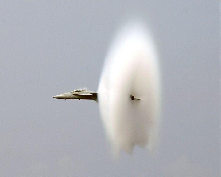 An F/A-18F Super Hornet shakes off a vapor cloud during a flight demonstration as part of a tiger cruise.