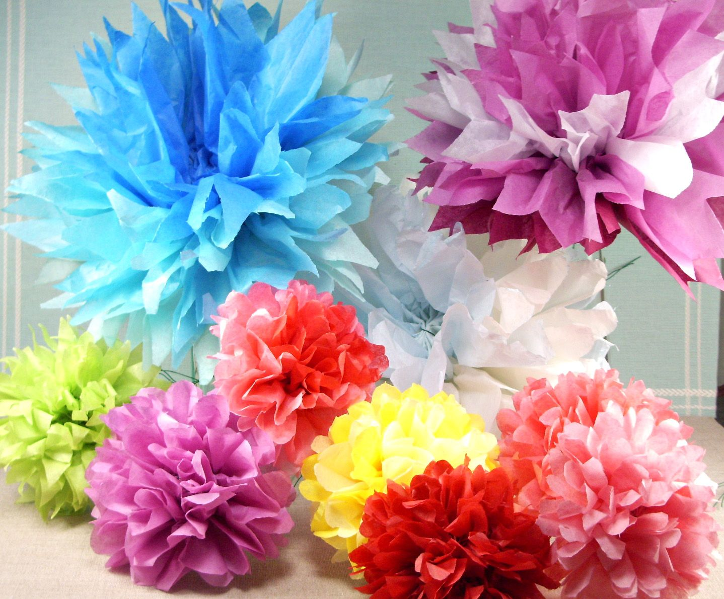I made large flowers like these for my room in madrid one year and make tissue paper flowers string them to long ribbon to make garland hang lots of garland strands just inside front door so guest walk through the wall mightylinksfo
