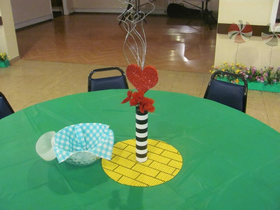 Wizard of Oz Party Decoration - yellow brick road placemat, witch leg vase, poppies, blue gingham napkin in the chip bowl, and a green table cloth for grass