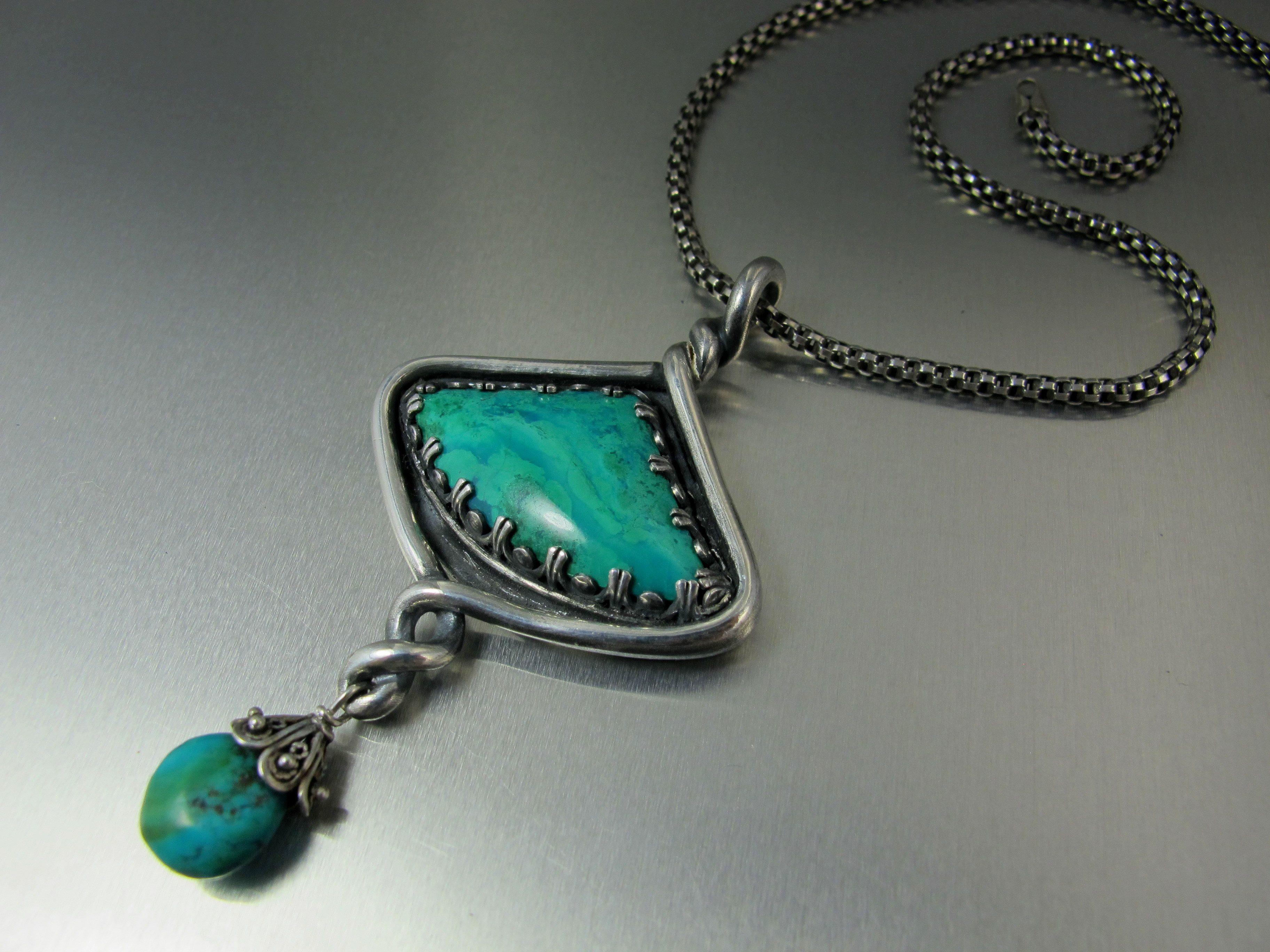 I did this piece with fine silver metal clay.  The bezel holding the stone is sterling gallery wire.  The focal stone is Chrysocolla with a turquoise dangle.