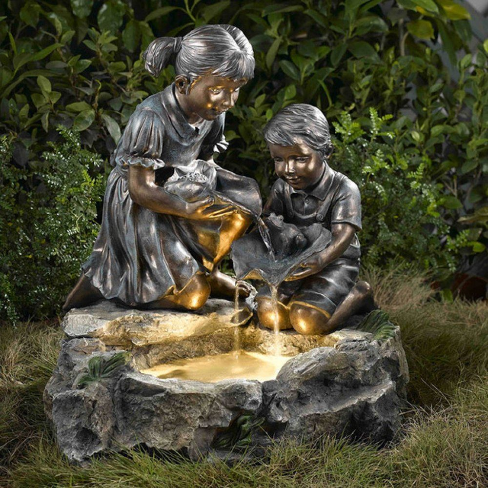 Hereu0027s A Backlit LED Outdoor Water Fountain With Sibling Statues.