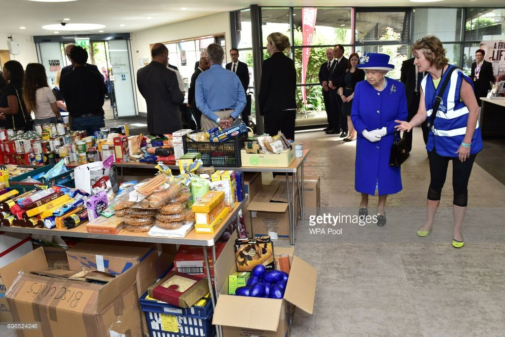 Queen Elizabeth II looks at donations to members of the