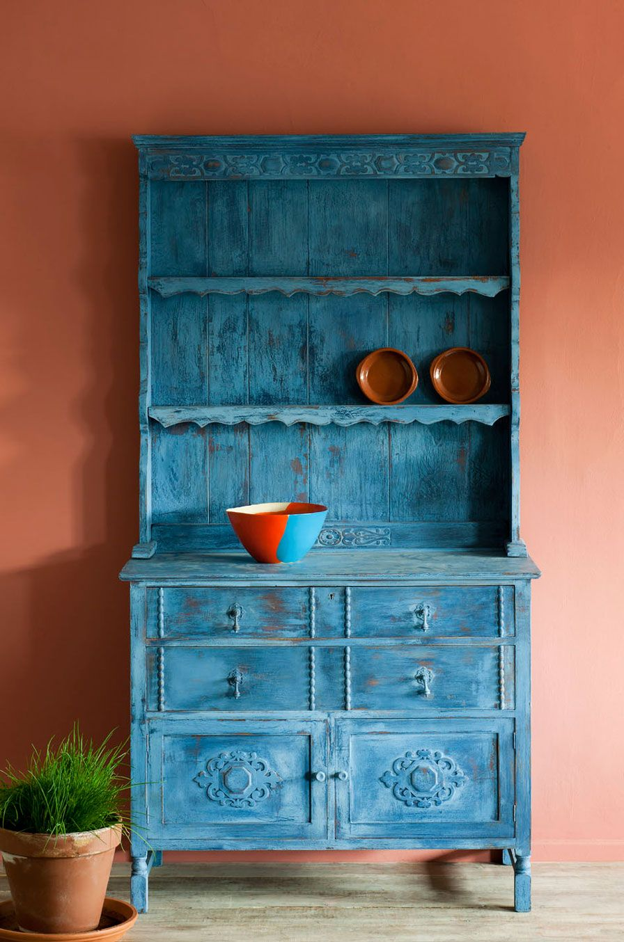 This dresser, probably 1940s, was given a distressed rustic finish, so that it wouldn't look out of place in an old farmhouse. Three colours from the Chalk Paint® palette were used: Primer Red, Napoleonic Blue, and Greek Blue. Sanding helped achieve the distressed look, revealing the different layers of colour, and exposing some of the wood, before being finished with Clear Soft Wax.
