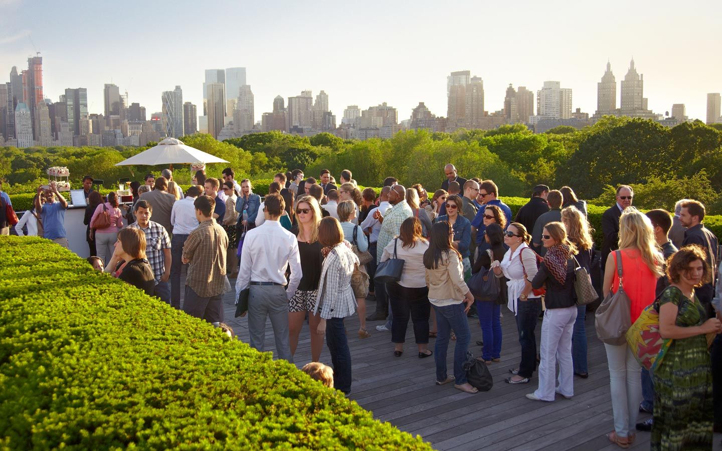 People Enjoying Drinks And Conversation On A Rooftop Bar With Views Of The Manhattan Skyline In The Backgr New York Attractions Rooftop Garden New York Rooftop