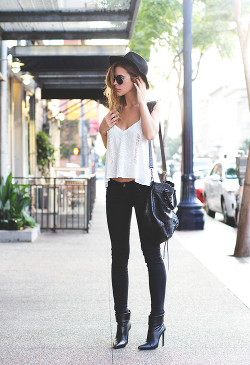 black and white street style with the loose fitting white top, black jeans,  black ankle heels, black shoulder bag, and a black hat to top off the outfit .